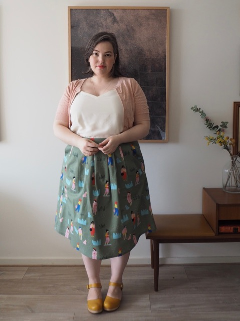 Woman wearing a white singlet, pink cardigan and printed green skirt
